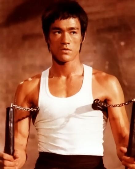 Bruce Lee wields nunchaku.