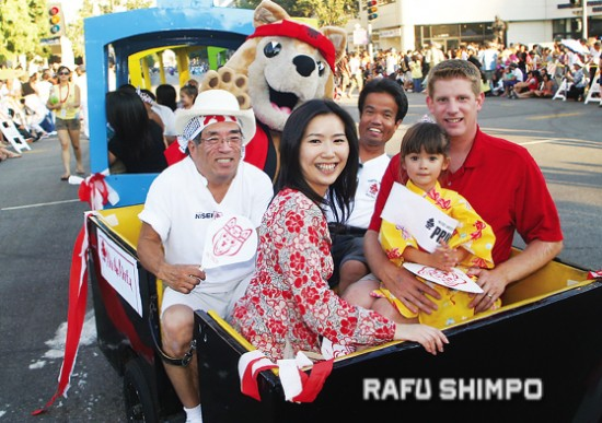 JT was heavily involved in Nisei Week, particularly in the coordination of the annual Baby Show. He is seen above riding a train in the 2007 Nisei Week Parade with one of the winning kids, her parents, Rodney Kageyama (left) and Aki the Akita. (MARIO G. REYES/Rafu Shimpo)