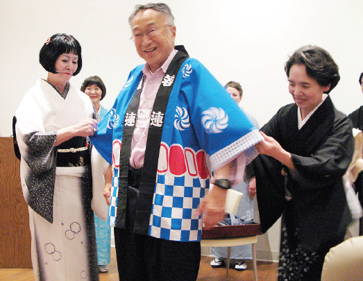 Dr. Paul Terasaki, founder of the Nibei Foundation, is given some help putting on a happi coat by Fumi Akutagawa (left) and Masako Kobayashi, president of the L.A. Kimono Club.
