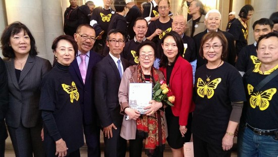 """(center), a surviving """"comfort woman,"""" was welcomed by supporters at San Francisco City Hall last year. Pictured from left: Julie Soo, Judge Lillian Sing, Supervisor Norman Yee, Supervisor Eric Mar, Supervisor Jane Kim, Judge Julie Tang, and Ignatius Ding of the Global Alliance to Preserve the Truth of Sino-Japanese War."""