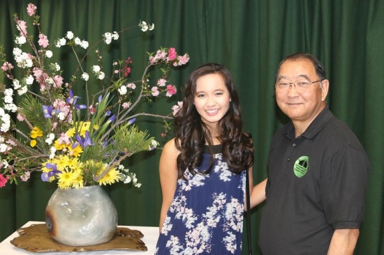 "Nisei Week Princess Kelsey Nakaji Kwong and SFVJACC President Paul Jonokuchi posing with ""Kibo"" (Hope), a flower arrangement designed by Ritsuko Shinbashi."
