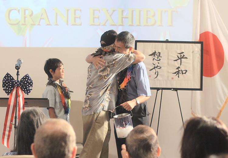 真珠湾の博物館で開かれた記念式典で禎子さんの折鶴が寄贈されるシーン。抱き合う退役米兵(左)と佐々木さん。左は、さとし