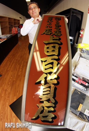 """Satoru """"Sats"""" Uyeda, whose father established the store, holds up a sign in Japanese. The top part says it is a good place to shop and you can find anything there. The large characters read, """"Ueda Hyakkaten"""" (Department Store)."""