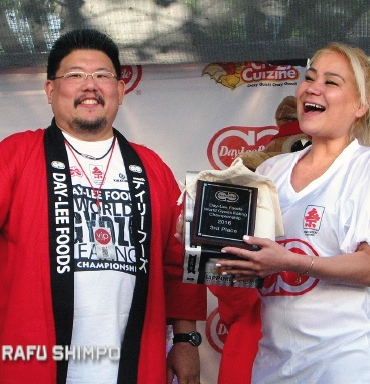 Sudo receives a plaque and a case of beer as her third-place prize from Day-Lee Foods' Jason Uno. (J.K. YAMAMOTO/Rafu Shimpo)
