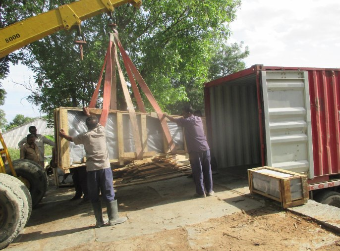 Workers in India load the obelisk into a shipping container.