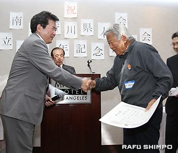 海外移住の高齢者として、県から表彰を受ける池田敬一さん(右)