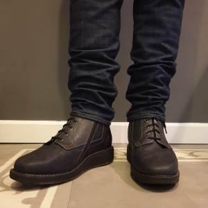 Orthopedische schoenen gedragen met spijkerbroek met koolstofvezel artrodesekokers enkelverstijving en zoolverstijving met rits
