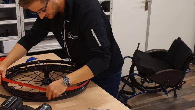 Afbeelding van een monteur van TNS die 25 inch rolstoelwielen met carbolife quadro hoepels klaar maakt voor montage op een rolstoel