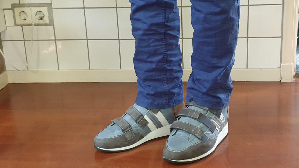 foto van hoge orthopedische schoenen met klittenband onder een blauwe broek met op de zijkant het logo van RaGaSto