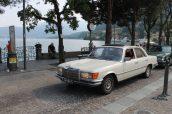 Foto van een witte Mercedes-Benz W116 met een rood interieur die over de boulevard van Menaggio flaneert