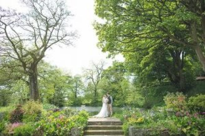 bride and groom stand near pond at The Ashes