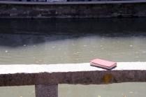 Un petit livre rouge laissé au bord du canal
