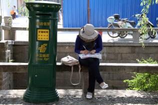 Une touriste écrit ses cartes postales