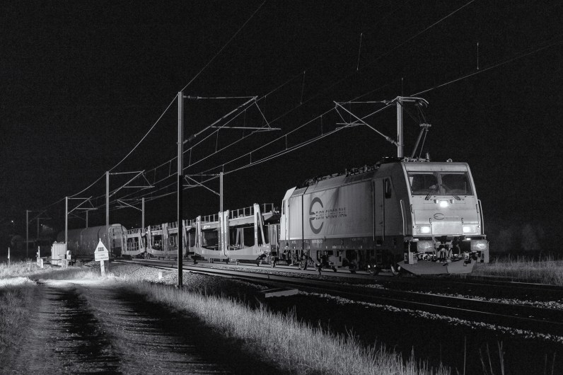 Night pictures processed in monochrome allow the viewer to appreciate the textures of the locomotives and the freight cars. One can also admire the sharp angles from this Bombardier Traxx-MS2e locomotive.