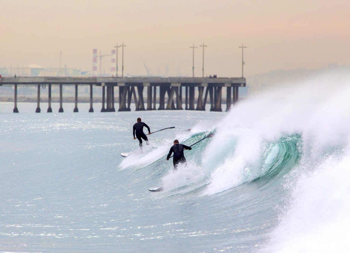 stand up paddle boarder wave riding