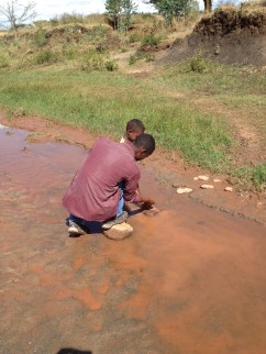 A young man and little boy at a water source