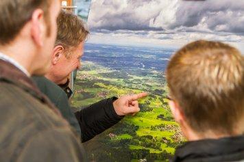 Ausstellungsbesucher betrachten eine Landschaftsaufnahme