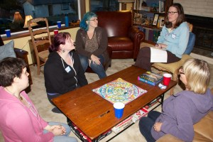 The group in the living room learning how to play the Psychic Circle game.  It helps to have one person taking notes and reading the book.  You can take turns doing this.