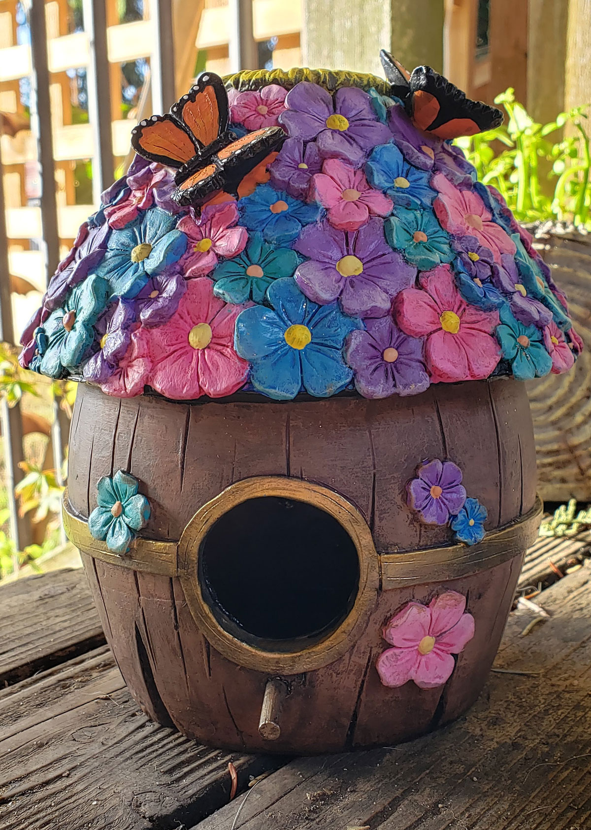 Front/side view of the finished flower barrel birdhouse with butterflies
