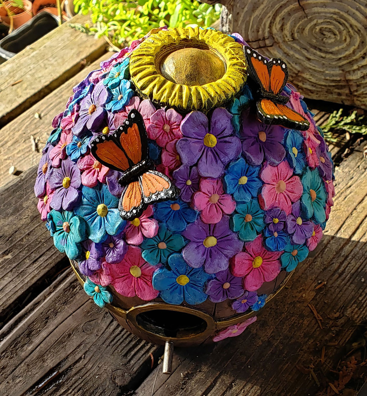 Top view of the finished flower barrel birdhouse with butterflies