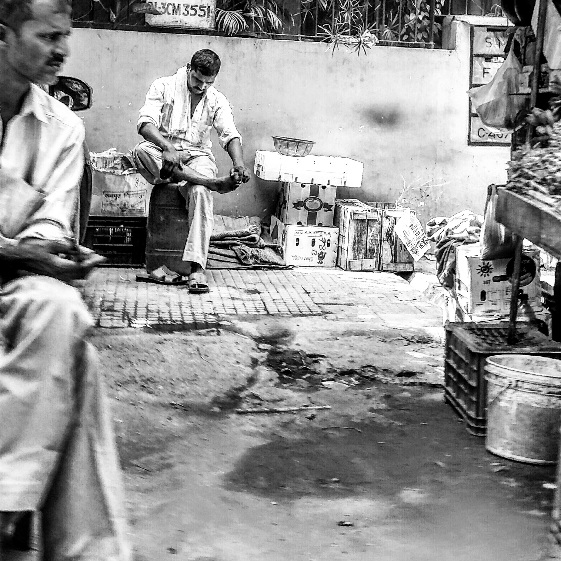A fruit-seller presses his own legs while another man looks on in the Chittaranjan Park area of South Delhi