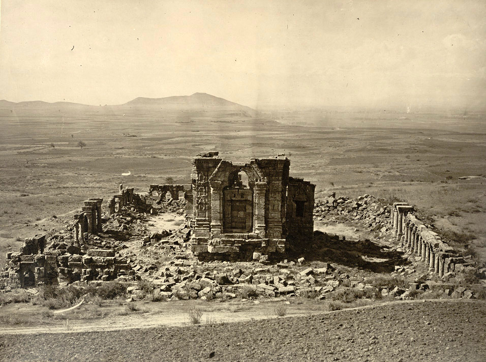 Kashmir. General view of Temple and Enclosure of Marttand or the Sun, near Bhawan. Probable date of temple A.D. 490-555. Probable date of colonnade A.D. 693-729 Photograph of the Surya Temple at Martand in Jammu & Kashmir taken by John Burke in 1868. This general view from the hillside looking down onto the ruins of the temple was reproduced in Henry Hardy Cole's Archaeological Survey of India Report 'Illustrations of Ancient Buildings in Kashmir.' (1869). Cole stated, 'The most impressive and grandest ruins in Kashmir, are at Marttand, which is about three miles east of Anantnag.' . The Surya temple is situated on a high plateau and commands superb views over the Kashmir valley. Dedicated to the sun god, it is considered a masterpiece of early temple architecture in Kashmir. It was built by Lalitaditya Muktapida (ruled c.724-c.760) of the Karkota dynasty, one of the greatest of Kashmir's rulers, under whom both Buddhism and Hinduism flourished. The temple consists of a principal sanctuary standing on a high plinth in a rectangular colonnaded court, surrounded by 84 small shrines. Its roof has disappeared but the immense doorway before the sanctum still stands, consisting of a trefoil arch set within a tall triangular pediment standing on engaged pilasters.
