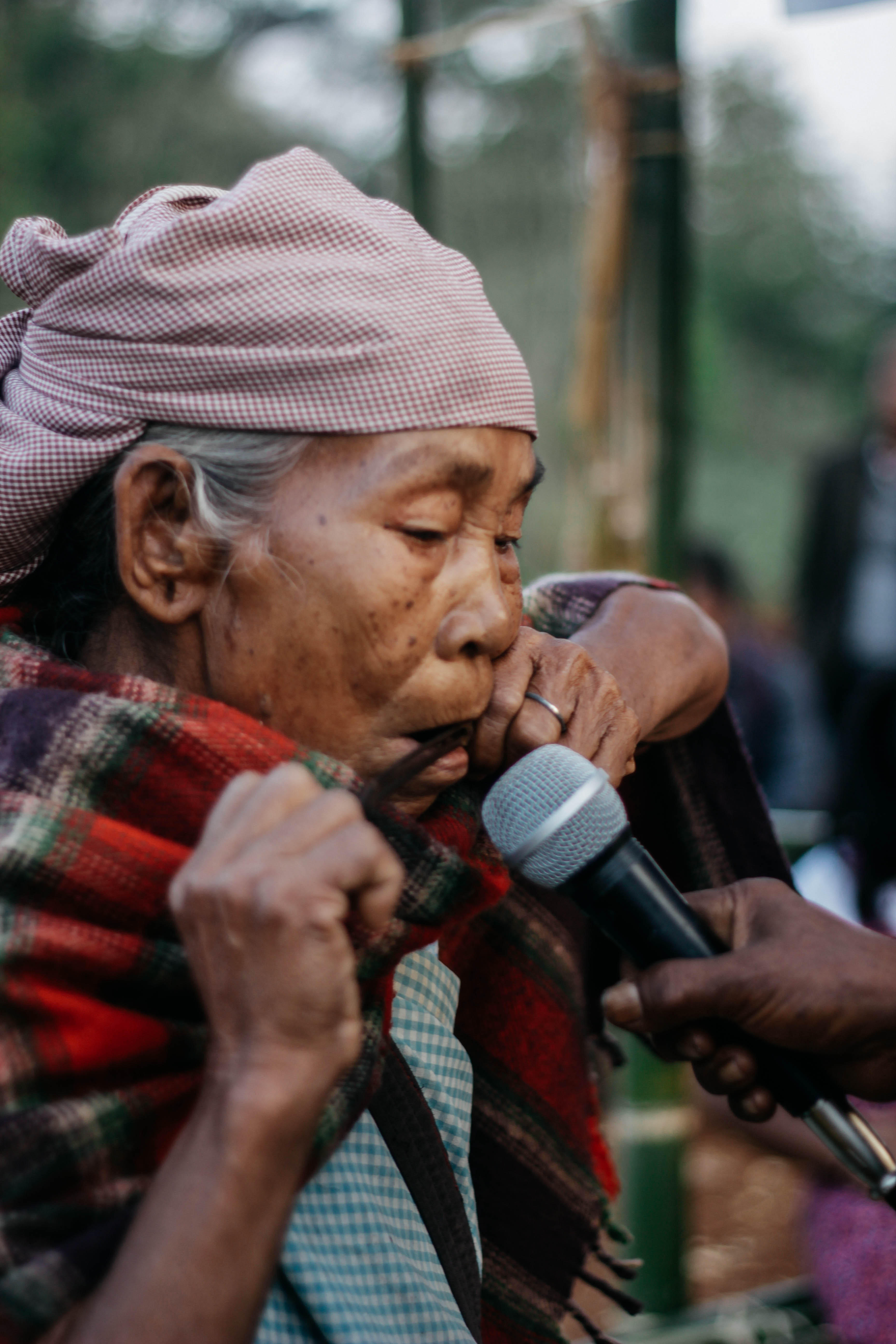 Old woman playing a jaw harp during the inaugural function