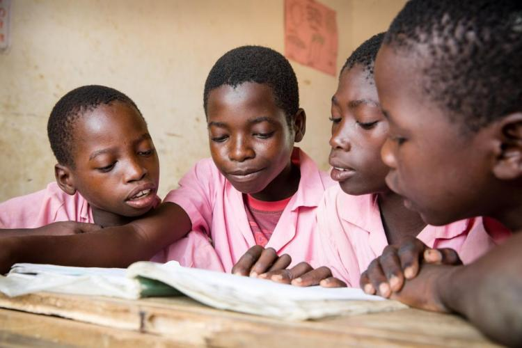 Students share a texbtook at Nyamachaki Primary School, Nyeri County, Kenya GPE/Kelley Lynch