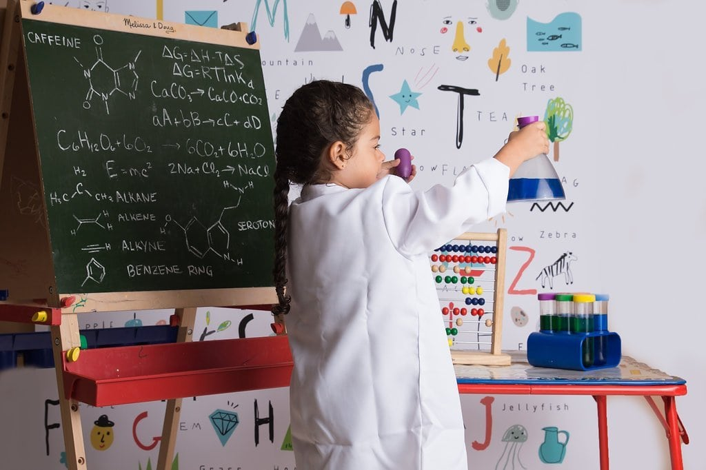 little girl dressed as scientist in front of letters and chalkboard with equations and symbols