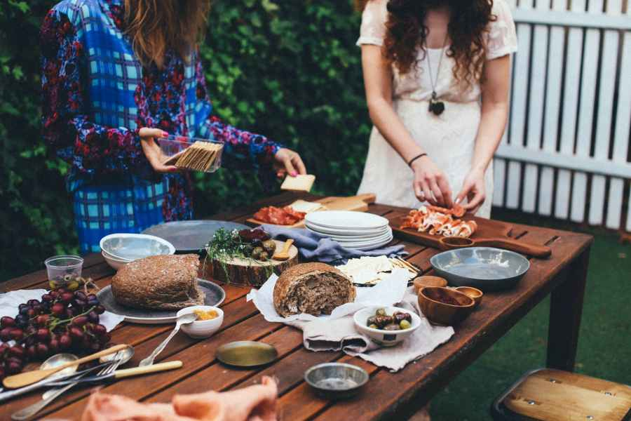 unrecognizable women serving table with assorted appetizers in garden