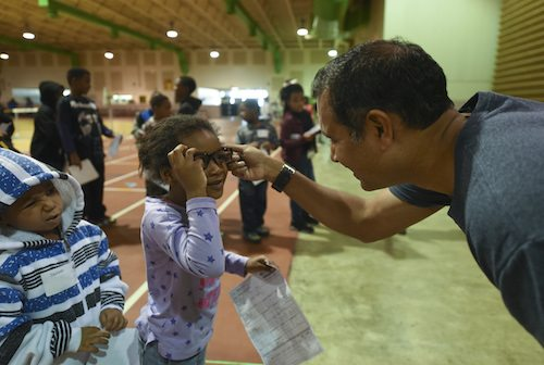 Man fitting a little girl with glasses