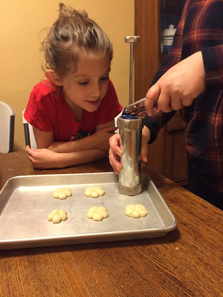 Pressing cookie dough onto baking sheet