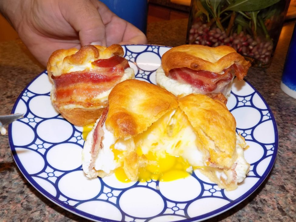Three breakfast sandwich scramblers on plate with one cut in half to show egg.