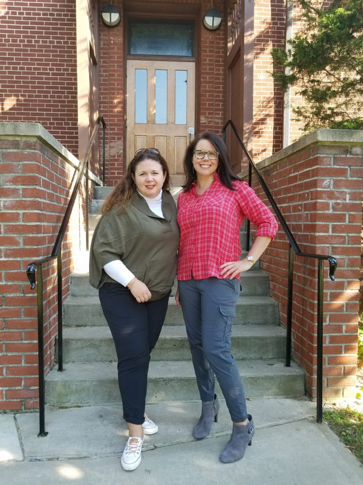 Two women standing in front of concrete stairs