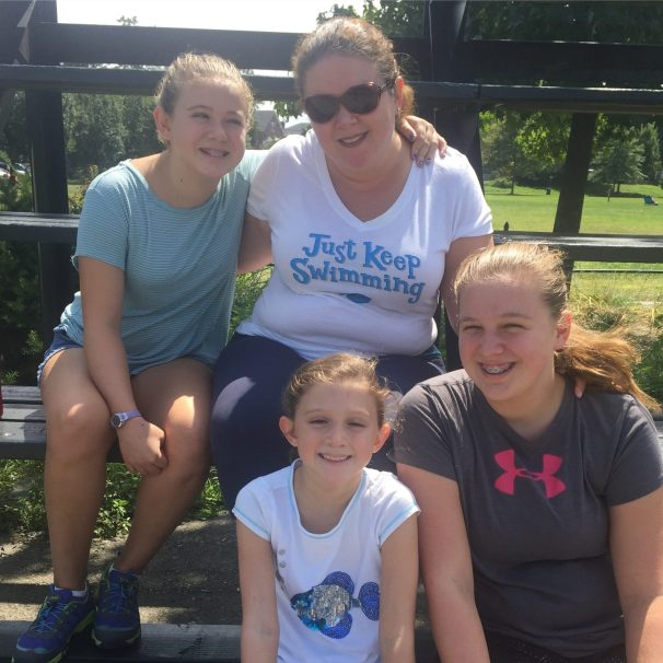 Woman and three daughters sitting on park bleachers