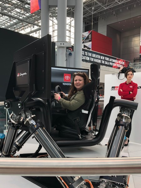 Woman sitting in the Toyota Supra simulator.