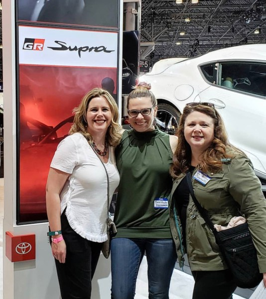 Three women posing next to the Toyota Supra.