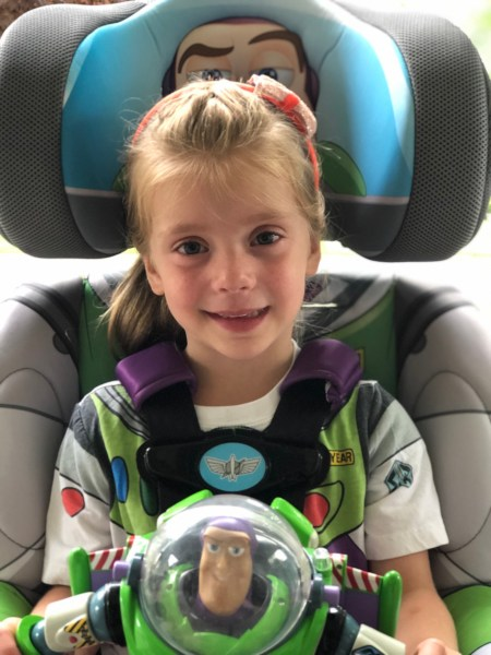 Girl sitting in Buzz Lightyear KidsEmbrace booster seat.