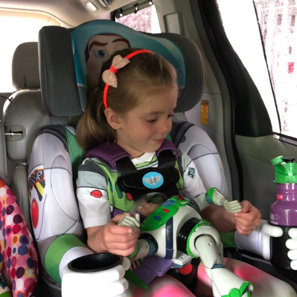 Girl with Buzz Lightyear toy sitting in the KidsEmbrace booster seat.