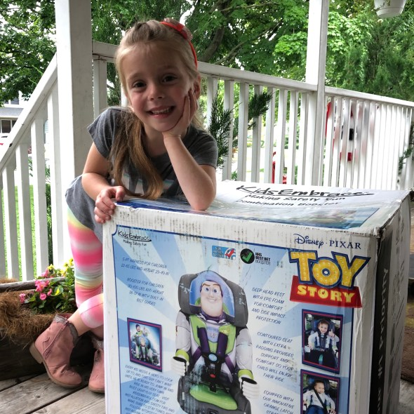 Girl standing next to Buzz Lightyear KidsEmbrace booster seat box.