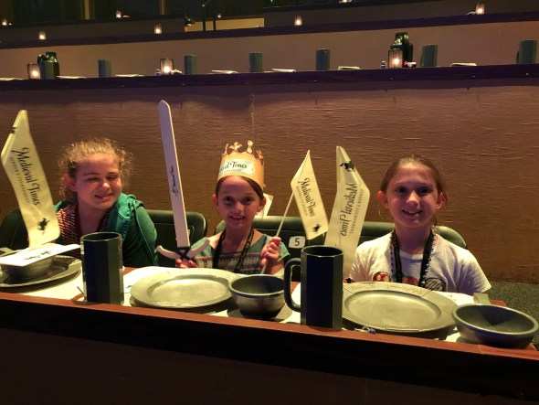 Three girls waiting for dinner in the seating area.
