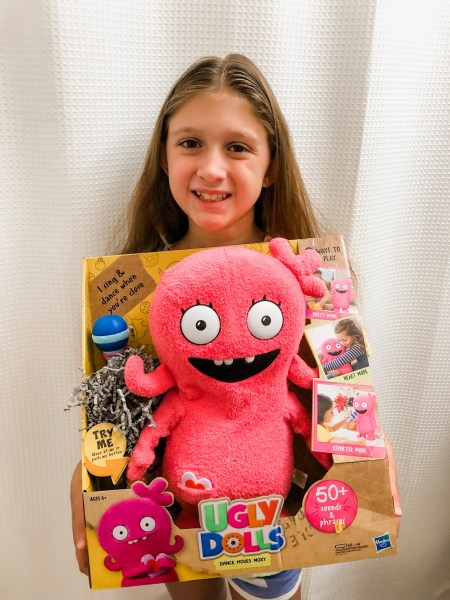 Girl holding UglyDolls Sing Along Edition plushie.