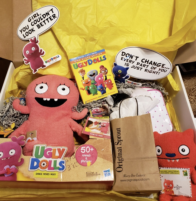 Box filled with UglyDolls Sing Along Edition plushies, games, and movie.
