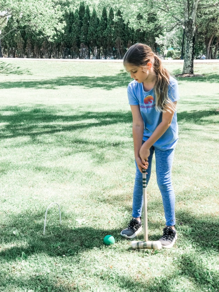 Girl playing croquet.