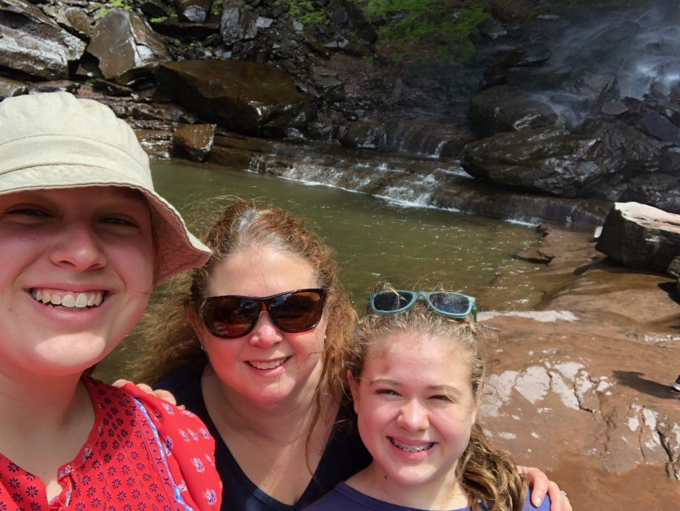 Mother and two daughters in front of a natural rocky pond.