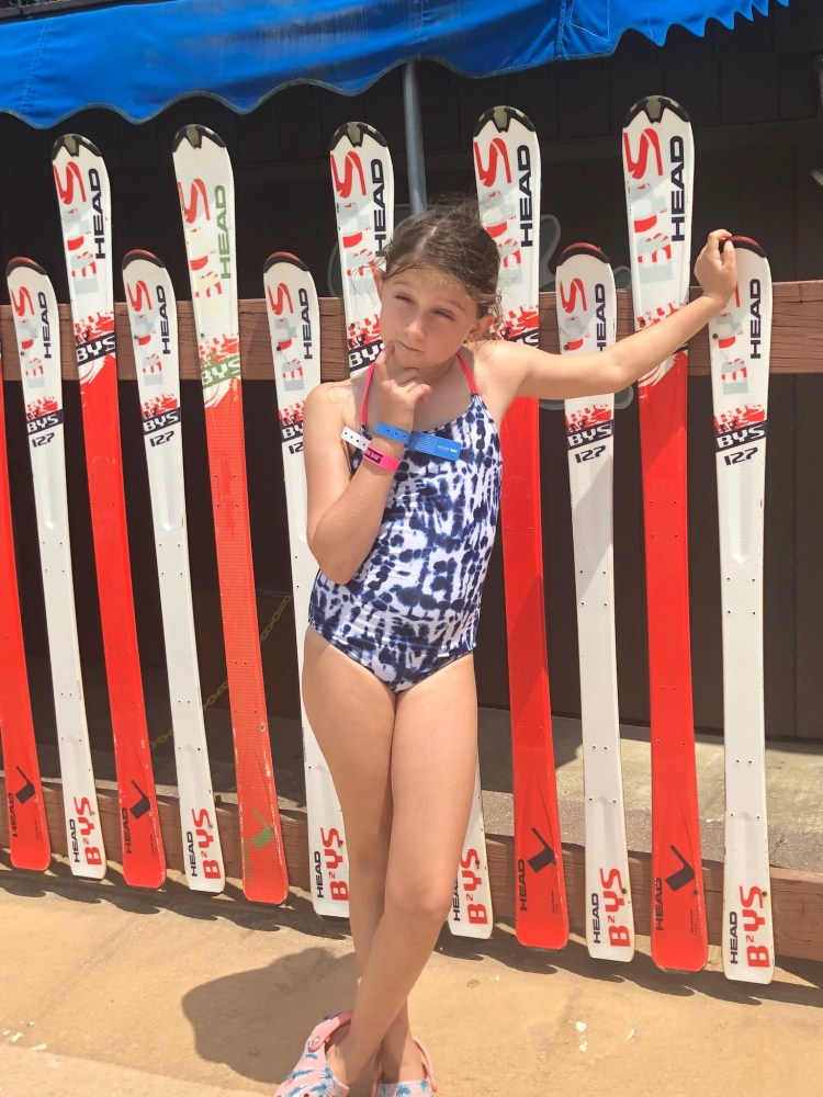 Girl standing in front of water ski rack.