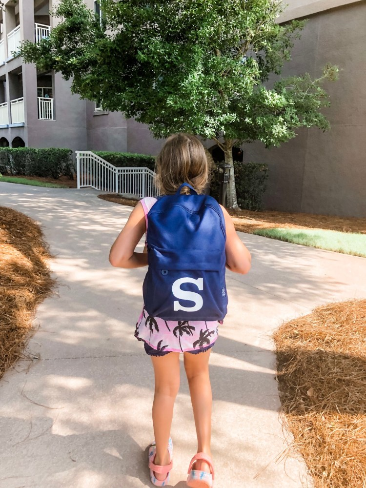 Girl wearing monogrammed backpack.