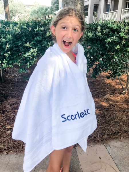 Girl with monogrammed towel wrapped around her.