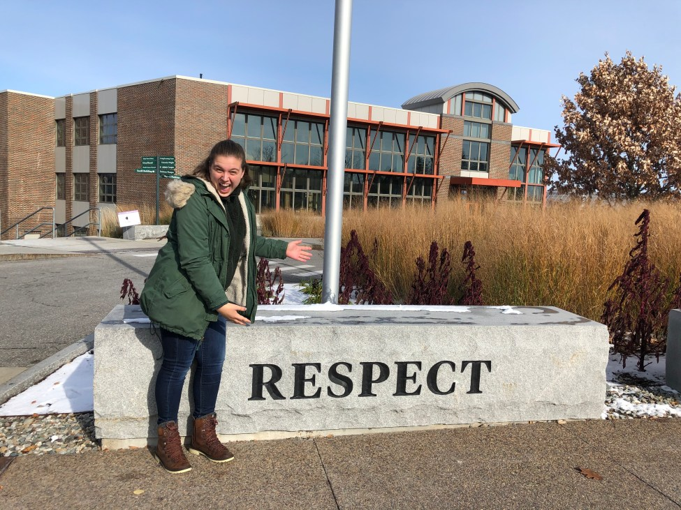 Girl standing next to college sign.