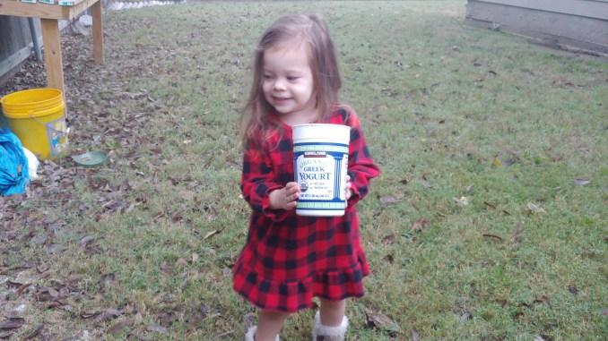 Child holding Kirkland Greek Yogurt tub